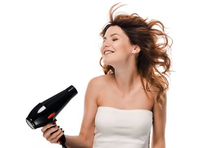 happy curly girl using hair dryer isolated on white