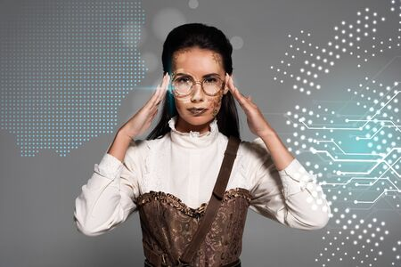 steampunk woman touching glasses isolated on grey with digital illustration Фото со стока