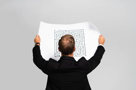 back view of businessman in suit looking at paper with labyrinth isolated on grey Reklamní fotografie