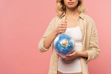 Cropped view of woman holding globe in polyethylene pack isolated on pink, global warming concept
