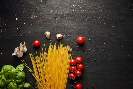 top view of raw bolognese pasta ingredients on black wooden background
