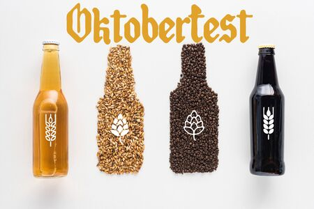 top view of bottles of dark and light beer near wheat and coffee grains isolated on white with Oktoberfest lettering