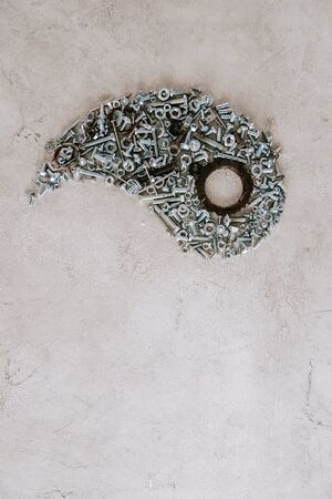 top view of aged metal screws arranged in part of taijitu symbol on grey background