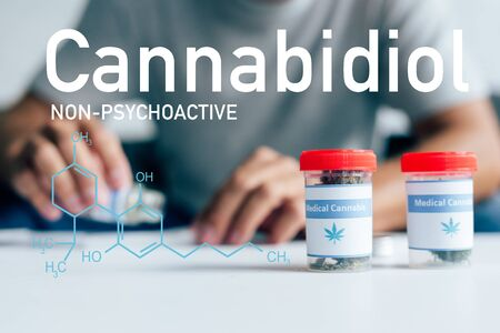 selective focus of bottles with medical cannabis on table with man on background with non-psychoactive cbd illustration