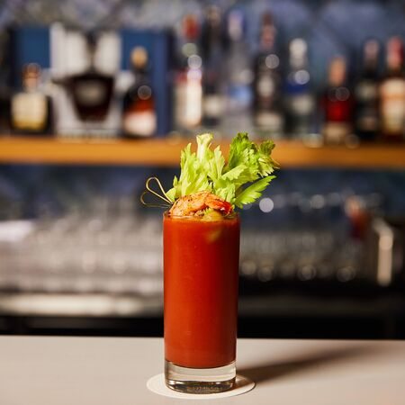 bloody mary cocktail with celery and shrimp in glass