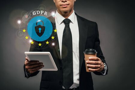partial view of african american businessman holding coffee to go and digital tablet on dark background with gdpr illustration