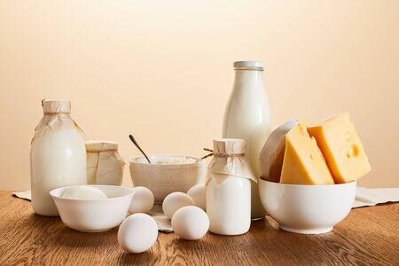 Sabrosos productos lácteos orgánicos y huevos en la mesa de madera rústica aislado en beige