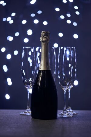bottle of sparkling wine and glasses with blue christmas lights bokeh