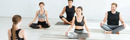 panoramic shot of five young people practicing yoga in half lotus pose