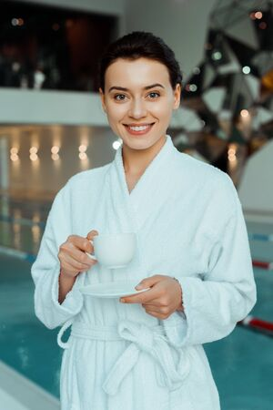 attractive and smiling woman in white bathrobe holding cup of coffee in spa