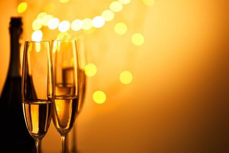 glasses and bottle of sparkling wine with yellow christmas lights bokeh