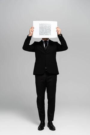 businessman obscuring face with paper with labyrinth on grey background Reklamní fotografie