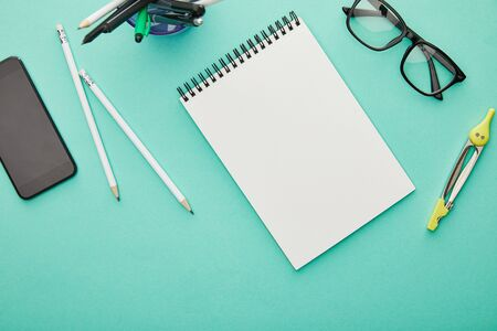 top view of smartphone with blank screen near glasses, stationery and notebook isolated on turquoise