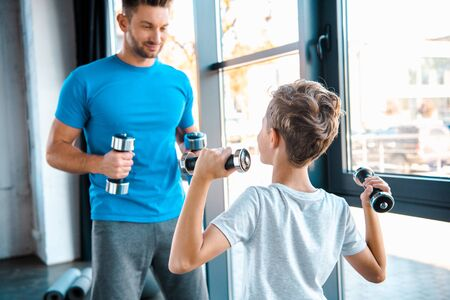 selective focus kid exercising with dumbbells near handsome father Banco de Imagens