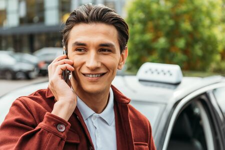Selective focus of smiling man talking on smartphone with taxi at background