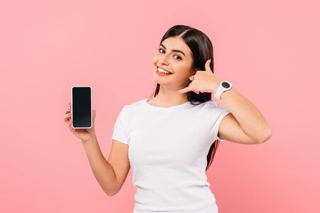 smiling pretty brunette girl holding smartphone with blank screen and showing call gesture isolated on pink