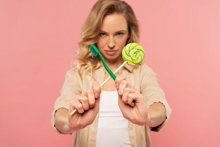 Blonde woman holding toothbrush and lollipop isolated on pink
