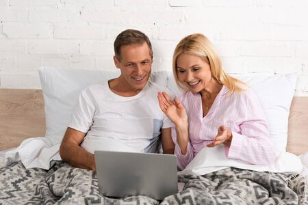 Smiling couple looking at laptop together in bed 스톡 콘텐츠