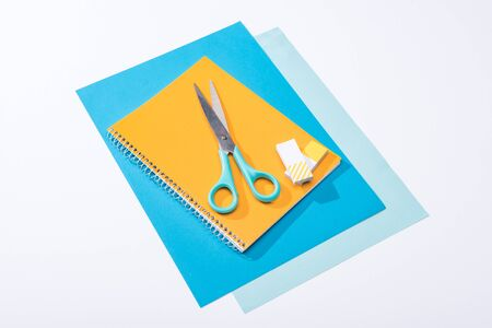 high angle view of scissors, notebook, erasers and paper isolated on white