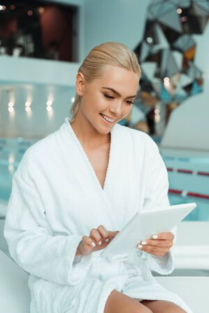 attractive and smiling woman in white bathrobe using digital tablet in spa