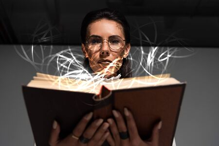 low angle view of pensive steampunk woman in glasses reading book with glowing illustration above