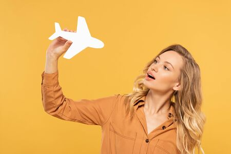 Blonde woman playing with paper plane isolated on yellow
