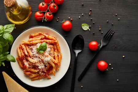 top view of tasty bolognese pasta with tomato sauce and Parmesan in white plate near ingredients and cutlery on black wooden background Фото со стока