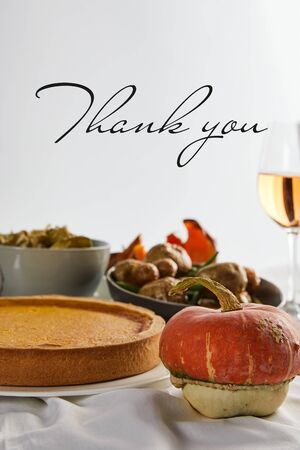 pumpkin pie, baked vegetables and whole pumpkin isolated on grey with thank you illustration