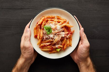cropped view of man holding plate with tasty bolognese pasta with tomato sauce and Parmesan on black wooden background
