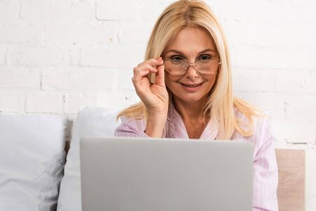 Smiling woman in eyeglasses using laptop in bed