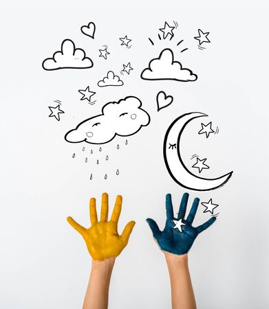 cropped view of child with blue and yellow paint on hands near moon and stars on white