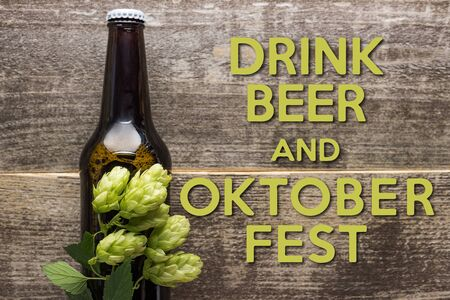 top view of fresh beer in bottle with green hop on wooden surface with drink beer and Oktoberfest lettering