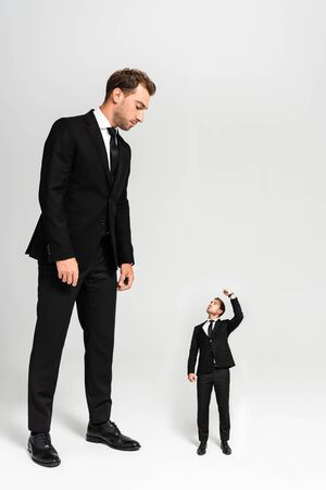 businessman in suit looking at marionette showing fist on grey background