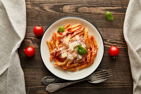 top view of tasty bolognese pasta with tomato sauce and Parmesan in white plate near ingredients and cutlery on wooden table Фото со стока