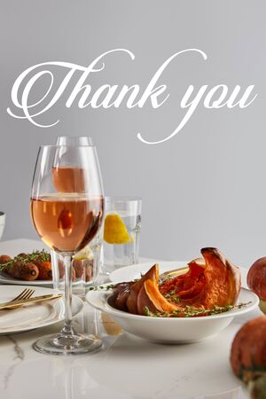 glasses with rose wine, baked pumpkin and carrots served on white marble table isolated on grey with thank you illustration