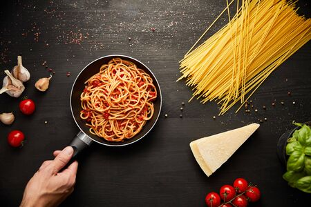 cropped view of man holding frying pan with tasty bolognese pasta near ingredients on black wooden background