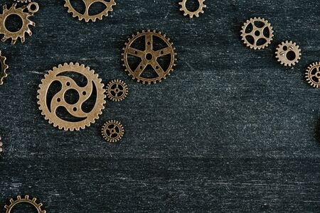 top view of vintage metal gears on dark wooden background with copy space