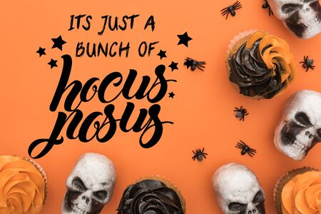 top view of cupcakes, decorative skulls and spiders on orange background with it is just a bunch of hocus pocus illustration