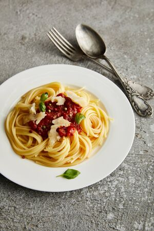 tasty bolognese pasta with tomato sauce and Parmesan on white plate near cutlery on grey background