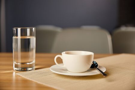 selective focus of cup of coffee near glass with water in cafe