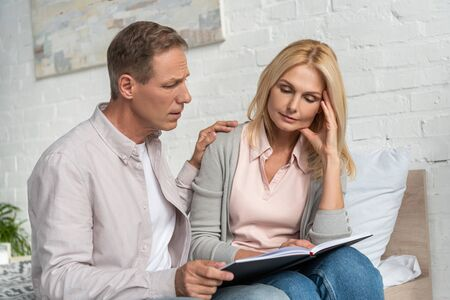 Man calming down thoughtful wife with notebook on bed Imagens