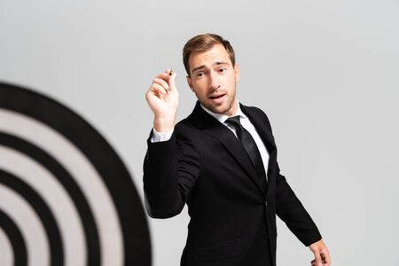 selective focus of businessman in suit playing darts isolated on grey