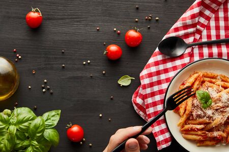 cropped view of man eating tasty bolognese pasta with tomato sauce and Parmesan from white plate on black wooden table with ingredients and check napkin