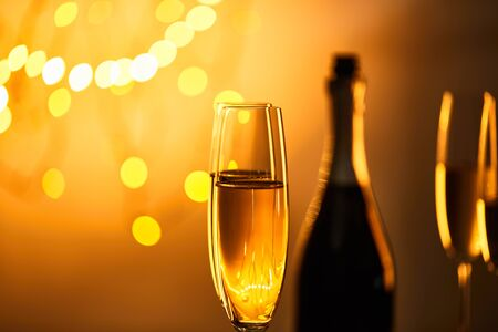 glasses of sparkling wine with blurred bottle and yellow christmas lights