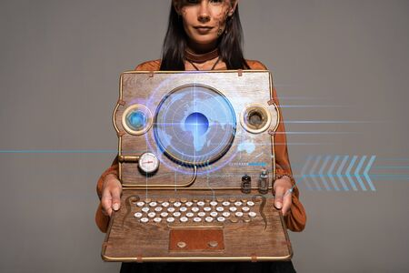 cropped view of steampunk woman in top hat with goggles showing vintage laptop with digital map isolated on grey Stock fotó
