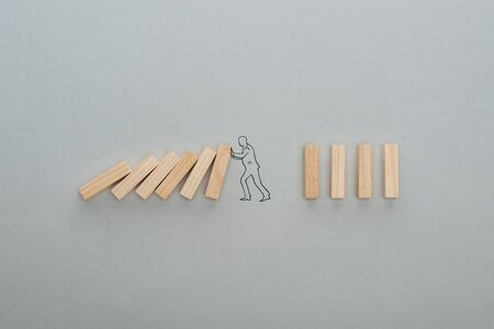 top view of drawn man pushing wooden blocks on grey background, business concept