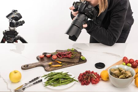 female photographer making food composition for commercial photography and taking photo on digital camera