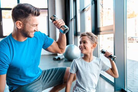 handsome father looking at cheerful son while exercising with dumbbell