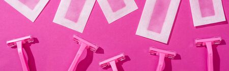 top view of disposable razors and wax depilation stripes on pink background, panoramic shot Foto de archivo - 134912005