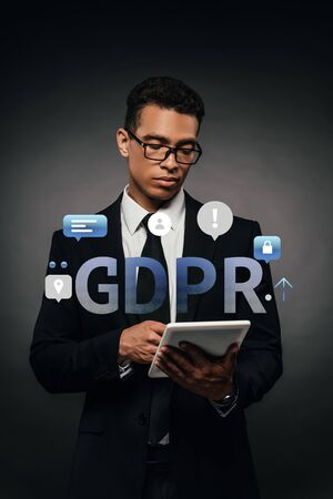 african american businessman in glasses using digital tablet on dark background with gdpr illustration Stock Photo
